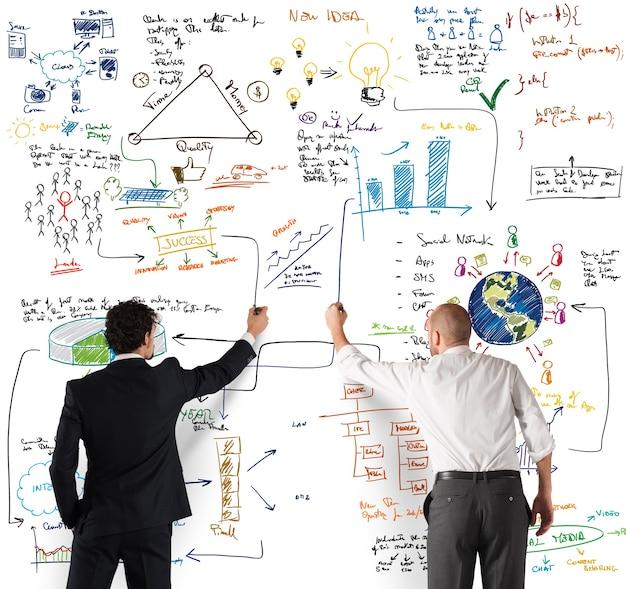 Equipe de negócios desenhando um novo projeto complexo na parede