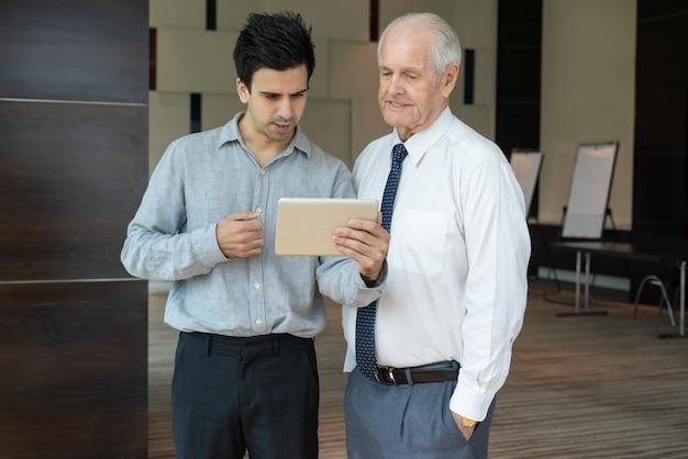 Equipe de negócios, discutindo dados sobre tablet