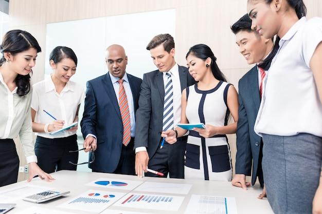 Equipe de negócios, discutindo gráficos e números em reunião