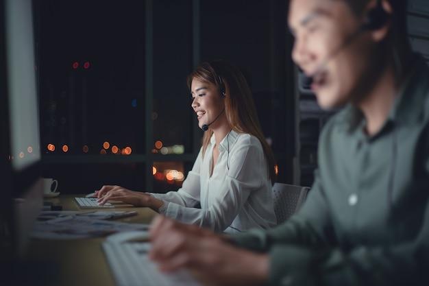 Equipe de negócios do operador de suporte ao cliente com fones de ouvido trabalhando tarde da noite no escritório.
