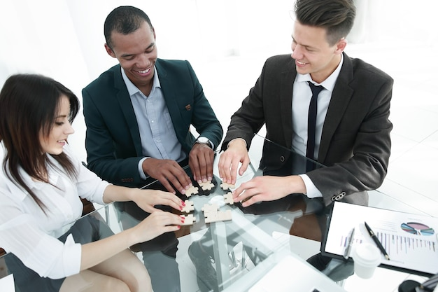 Equipe de negócios dobrando as peças do quebra-cabeça sentado atrás da mesa
