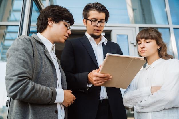 Equipe de negócios dois homens e mulher trabalhando juntos lá fora.
