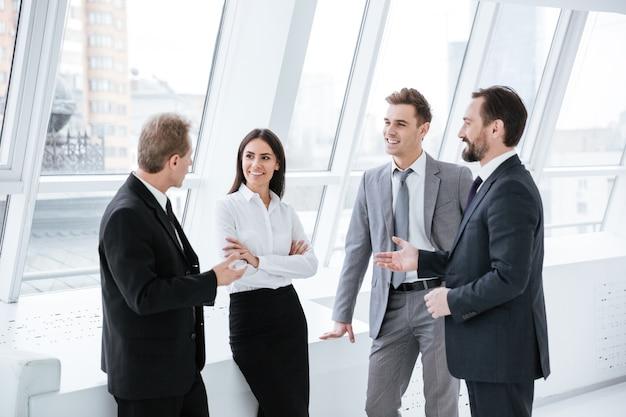 Equipe de negócios em pé e falar perto da janela na sala de conferências