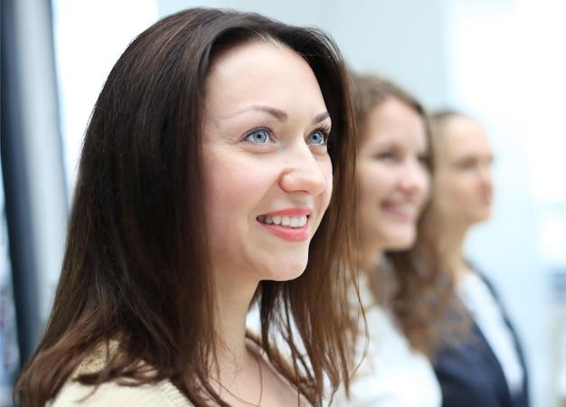 Equipe de negócios em pé em uma fileira no escritório e olhando para cima - equipe de negócios de sucesso