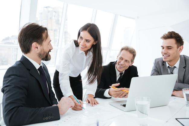 Equipe de negócios falando ao lado da mesa. mulher em pé perto da mesa. homens sentados