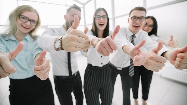 Equipe de negócios feliz mostrando os polegares.