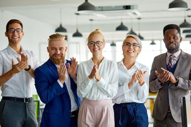 Equipe de negócios feliz parabeniza colega com um bom trabalho por fazer um projeto de sucesso