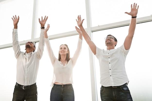 Equipe de negócios feliz reunida e levantando as mãos