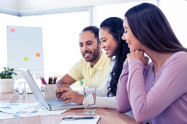 Equipe de negócios feliz trabalhando sobre laptop na sala de conferências no escritório criativo