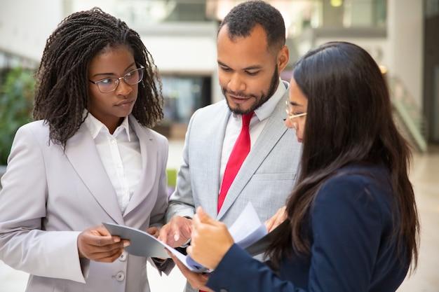 Equipe de negócios focada lendo acordo juntos