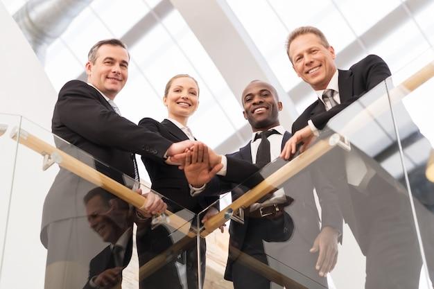 Equipe de negócios forte. visão de baixo ângulo de quatro empresários confiantes, próximos uns dos outros e de mãos dadas