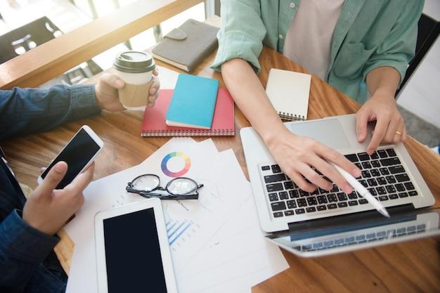 Equipe de negócios, informando a estratégia de marketing com telefone inteligente, tablet, notebook e laptop