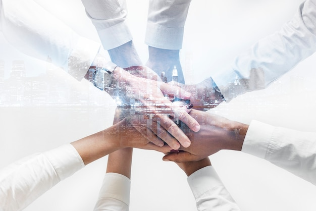 Equipe de negócios juntando as mãos fundo da cidade