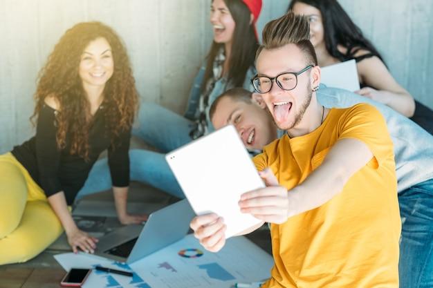 Equipe de negócios milenar trabalhando juntos. grupo de jovens diversos sentado no chão.