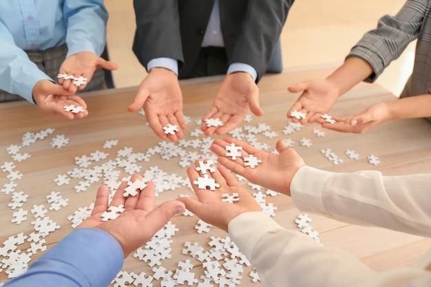 Equipe de negócios montando quebra-cabeça em mesa de madeira