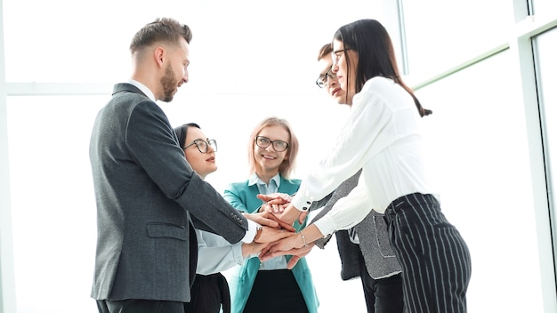 Equipe de negócios mostrando sua unidade em pé no escritório. o conceito de trabalho em equipe