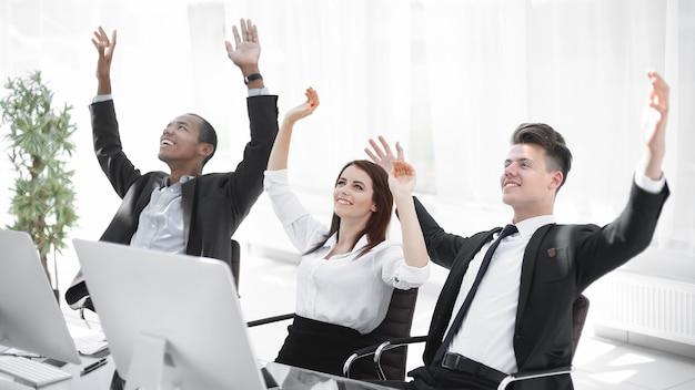 Equipe de negócios muito feliz sentada na mesa