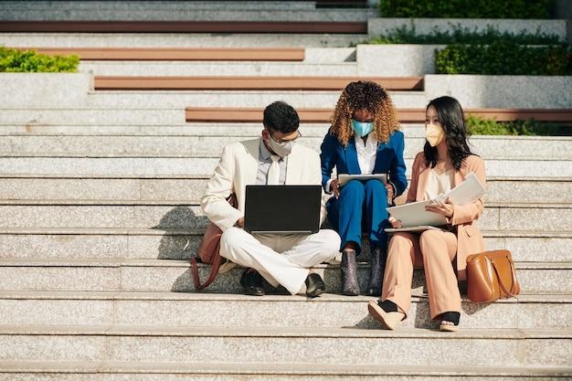 Equipe de negócios multiétnica com máscaras médicas sentada nos degraus com laptop e documentos e trabalhando juntos no projeto
