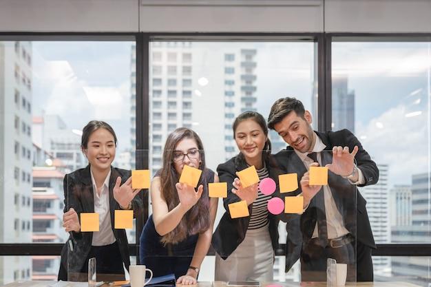 Equipe de negócios multiétnica fazendo brainstorming com nota de postagem