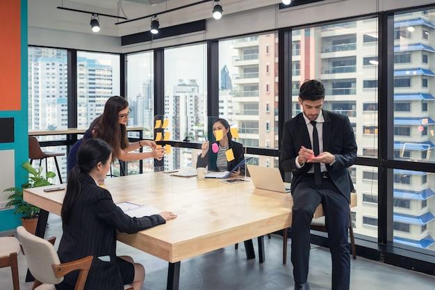 Equipe de negócios multiétnica fazendo brainstorming com post it colado no quadro de conferências no espaço de coworking no distrito comercial