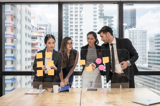 Equipe de negócios multiétnica fazendo um brainstorming e discutindo a bordo no escritório