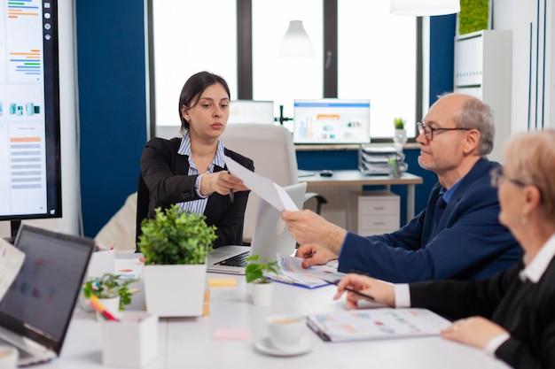 Equipe de negócios multiétnica sentada à mesa no centro do escritório falando sobre o projeto durante a reunião em sala ampla