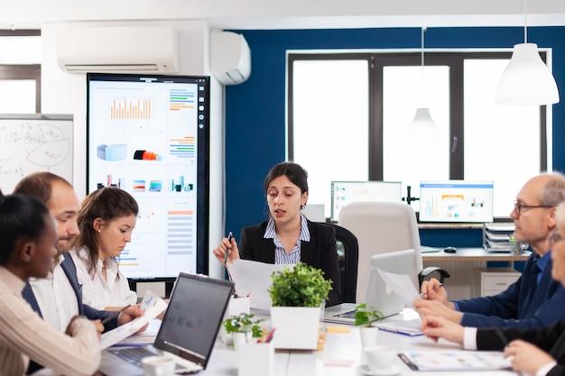 Equipe de negócios multiétnica sentada à mesa no centro do escritório falando