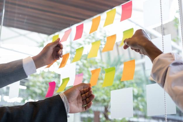 Equipe de negócios olhar as notas adesivas na parede de vidro na sala de reuniões