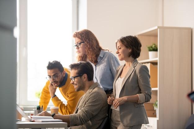 Equipe de negócios pensativa olhando para a tela do laptop enquanto visualiza a maquete do projeto com o web designer de conteúdo em um escritório moderno