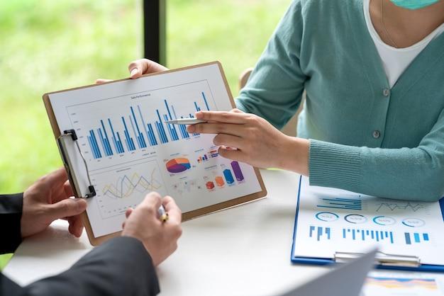 Equipe de negócios segurando um gráfico apontando para o trabalho de contabilidade estatística de apresentações de gráfico na reunião.