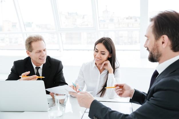 Equipe de negócios sentada à mesa com laptops em conferência no escritório