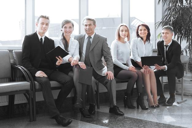 Equipe de negócios sentada no saguão do escritório