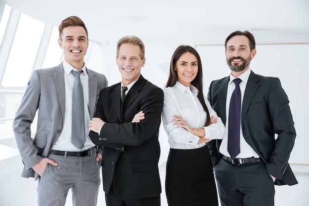 Equipe de negócios sorridente em pé no escritório e olhar para a câmera