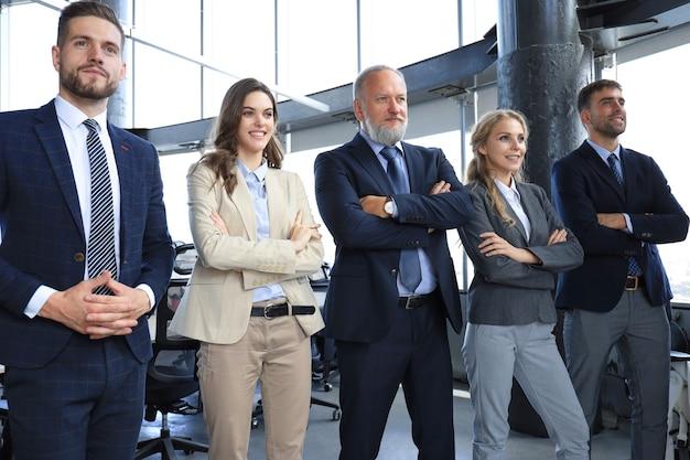 Equipe de negócios sorridente feliz em pé em uma fileira no escritório.
