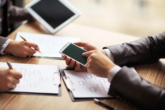 Equipe de negócios trabalhando em um esquema de negócios usando o tablet e smartphone