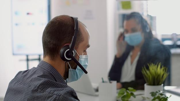 Equipe de negócios usando máscaras protetoras e fone de ouvido, trabalhando no computador durante a epidemia global de covid19. colegas de trabalho mantendo o distanciamento social para prevenir doenças virais