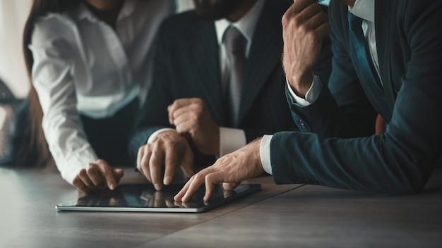 Equipe de negócios usando tablet digital juntos. mãos de empresários tocando a tela do dispositivo eletrônico. imagem tonificada. close-up tiro. vista lateral.
