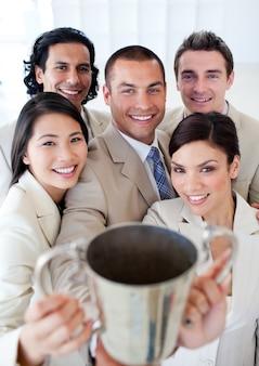 Equipe de negócios vitorioso mostrando seu throphy