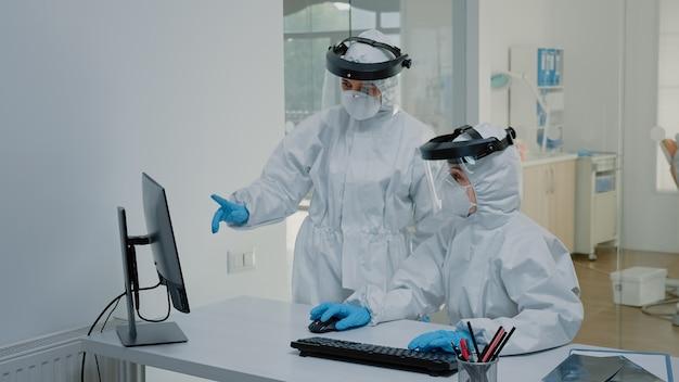 Equipe de odontologia vestindo ternos de ppe discutindo radiografia dentária