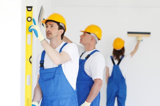 Equipe de operários pintando parede
