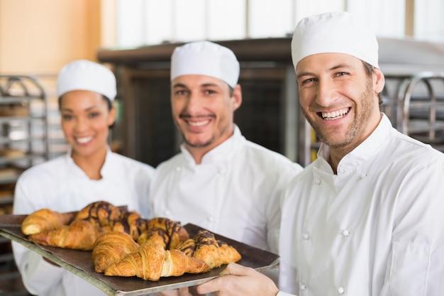 Equipe de padeiros sorrindo na câmera com bandejas de croissants