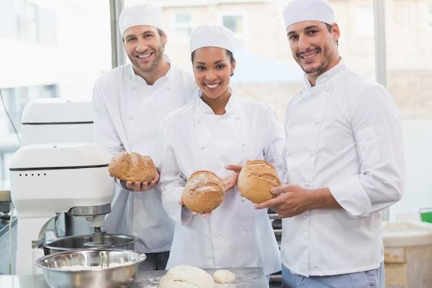 Equipe de padeiros sorrindo na câmera segurando pão