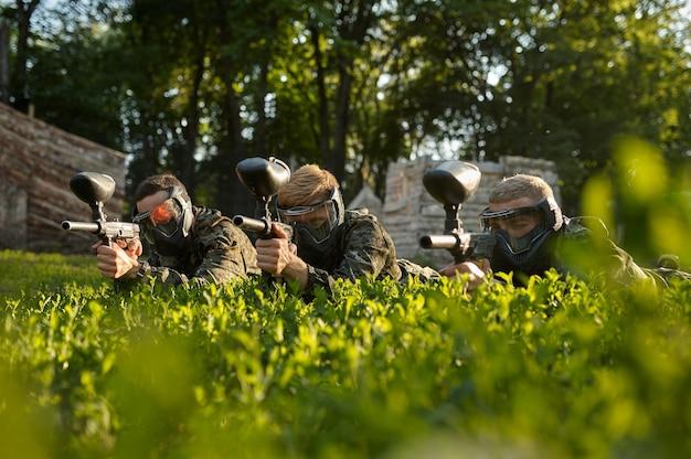 Equipe de paintball com máscaras, batalha no playground na floresta. esporte radical com arma pneumática e balas ou marcadores de tinta, jogo militar ao ar livre, táticas de combate