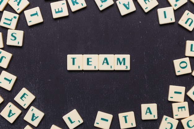 Equipe de palavras em letras scrabble sobre pano de fundo preto