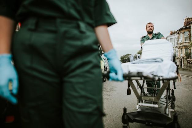 Equipe de paramédicos rolando uma maca na rua