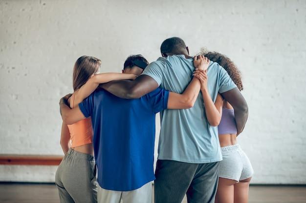 Equipe. de pé de costas, abraçar os jovens em roupas casuais é uma atitude amistosa e unida