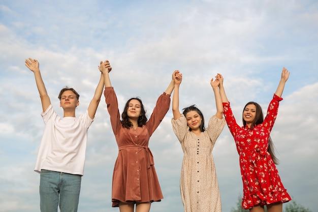 Equipe de pessoas com as mãos para cima