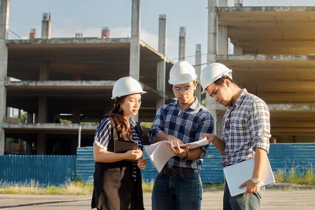 Equipe de pessoas de arquitetos no grupo no local de construção verificar documentos