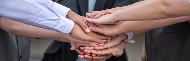 Equipe de pessoas de negócios empilhando as mãos e o conceito de trabalho em equipe.