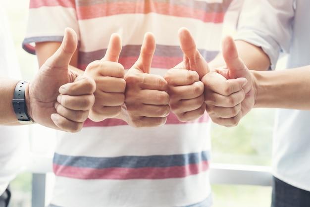Equipe de pessoas de negócios mostram thump juntos para sinal de acordo